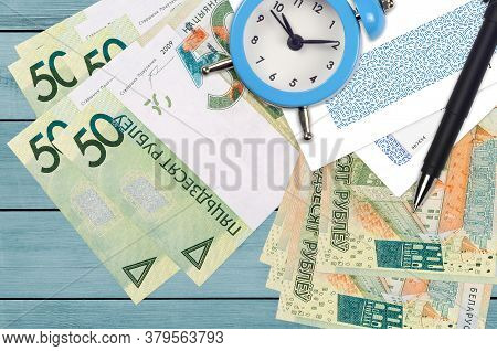 50 Belorussian Rubles Bills And Alarm Clock With Pen And Envelopes. Tax Season Concept, Payment Dead