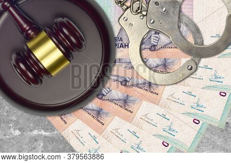 1000 Indonesian Rupiah Bills And Judge Hammer With Police Handcuffs On Court Desk. Concept Of Judici