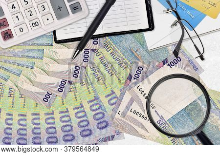 1000 Indonesian Rupiah Bills And Calculator With Glasses And Pen. Tax Payment Season Concept Or Inve
