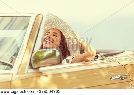 Smiling Woman Enjoying Her Summer Cabrio Ride Holding Her Hat With One Hand.