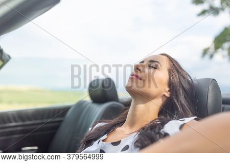 Woman Sitting In A Cabrio Car Smiling, Eye Closed, Having A Rest And Nap.