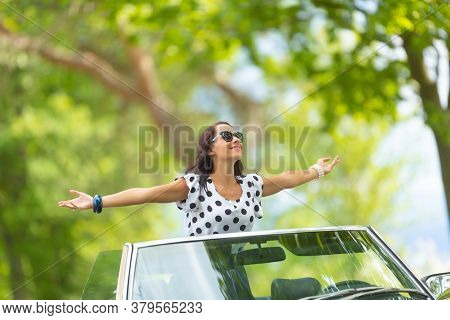 Woman In Sunglasses Sits On Top Of The Convertible, Arms Wide Open, Soaking Up The Sun And Fresh Air