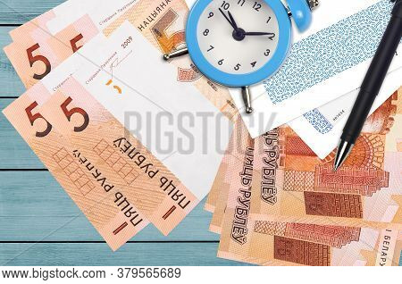 5 Belorussian Rubles Bills And Alarm Clock With Pen And Envelopes. Tax Season Concept, Payment Deadl