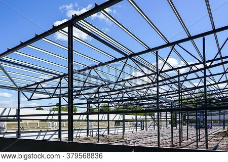 Construction Of A New Modern Industrial Building, Metal Truss Frame On A Background Of Blue Sky