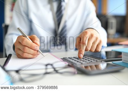 Close-up Of Busy Person Press Knobs On Calculator. Serious Office Worker Prepare Monthly Report. Pro