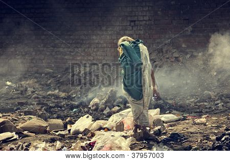Pollution and poverty : Indian old female searching food for herself in  garbage, poster
