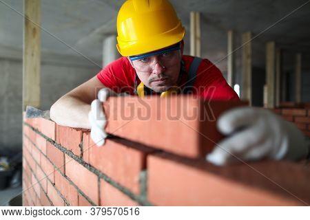 Builder Carefully Puts Red Brick On The Masonry. Quick Work Bricklayer. Guy Measures Level Masonry.