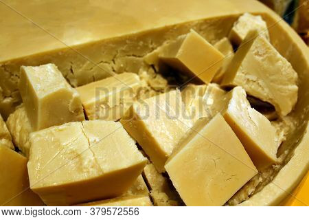 Parmesan Cheese Chopped Into Slices Inside A Cheese Circle. Prepared For Sale. In The Shop Window. A