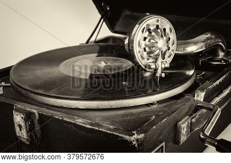 Portable Wind-up Gramophone. Phonograph With Crank. Old Gramophone With A Plate Record Isolated On A
