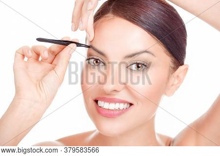 Young Woman Plucking Eyebrows Hair With Tweezers Close Up Portrait Studio Shot Isolated On A White B