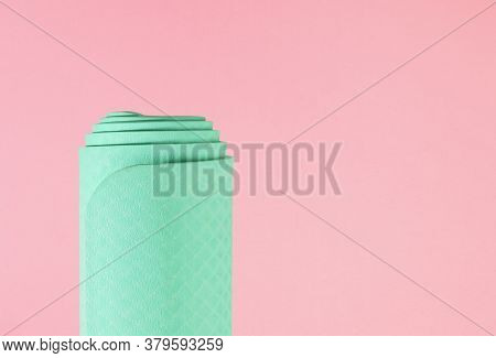 Rolled Yoga Gym Mat Isolated Against A Pink Baclground, Health And Fitness Concept With Copy Space