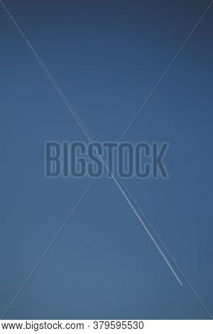 Flying Airplane Trail In A Clear Sky