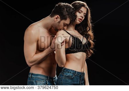 Handsome Man Kissing Shoulder Of Sensual Woman In Bra Isolated On Black Background