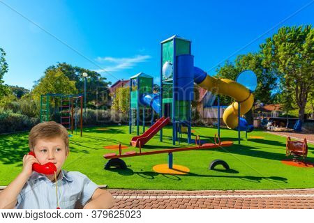 Handsome boy with blue eyes speaks on a red telephone. Great kids playground. Attraction