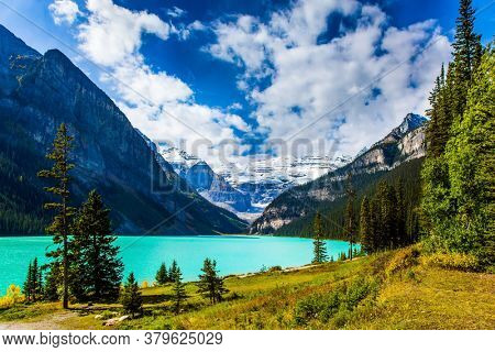 The lake with azure water is surrounded by mountains and forests. Glacial Lake Louise in Banff, Canadian Rockies. Sunny fine day. The concept of ecological, active and photo tourism