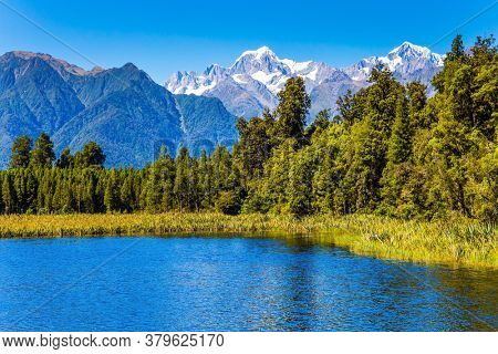 Lake Matheson is a beautiful glacial lake. The South Island of New Zealand. The famous lake reflects Mount Cook and Mount Tasman. The concept of ecological, active and photo tourism
