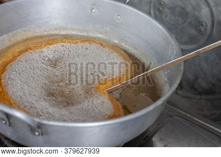 Making Thai Dessert Golden Egg Yolk Threads (foi Thong) In A Pot With Boiling Syrup.