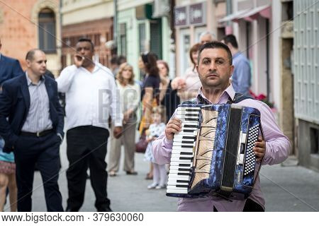 Novi Sad, Serbia - June 12, 2016: Accordionist With His Accordion Standing In Front  Roma Band Playi