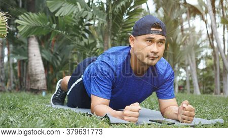 Mature Asian Man Fit And Plank Exercise On The Grass In The Park. Sportsman Wearing Sportswear, Fitn