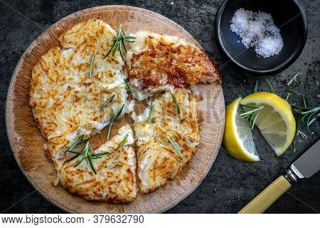 Potato rosti on old board, with salt, lemon and herbs.  Swiss potato, top view.