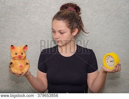 A Young Girl Holds A Watch In One Hand And A Piggy Bank In The Other, Looks At The Piggy Bank And Po