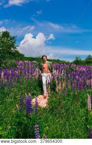 Tall Handsome Man Walking On A Pink Cloth In Lupine Flowers Field