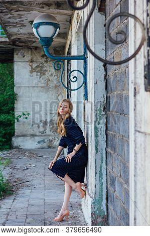 Young Woman Standing Next To An Old Building