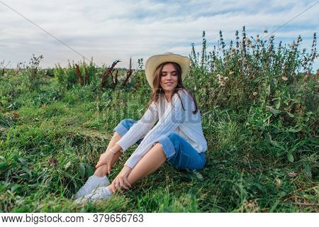 Young Beautiful Brunette Woman Sitting On The Grass And Smiling