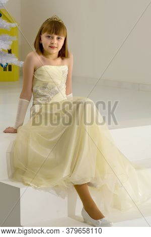 A Charming Little Girl In A Smart Dress Sits On A White Staircase. The Concept Of Happiness, Childho