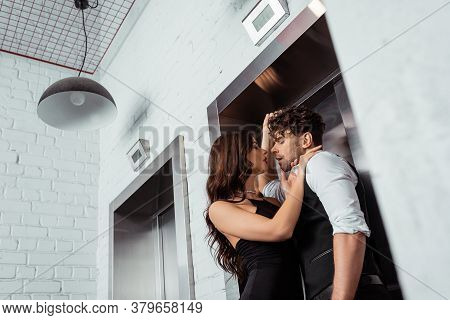 Focus Of Woman Hugging Handsome Man In Shirt And Waistcoat Near Elevator