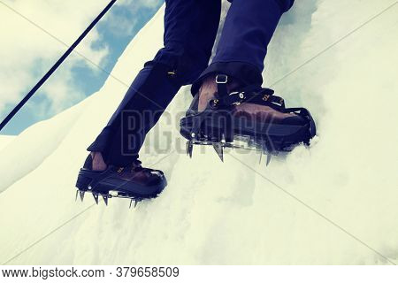 Close up of climber climbing ice mountain in mountainering  shoes