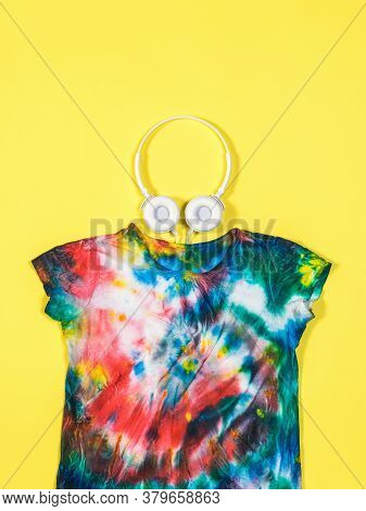 White Headphones And A Tie Dye T-shirt On A Yellow Background. White Clothes Painted By Hand. Flat L