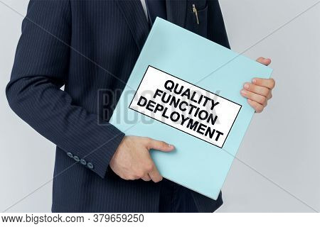 Business Concept. A Businessman Holds A Folder With Documents, The Text On The Folder Is - Quality F