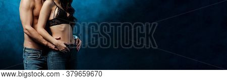 Panoramic Crop Of Muscular Man Embracing Woman In Jeans And Bra On Black Background With Smoke