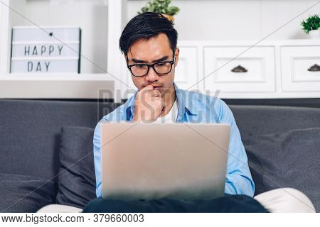 Young Asian Man Relaxing Using Laptop Computer Working And Video Conference Meeting At Home.young Cr