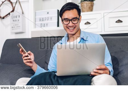 Young Smiling Asian Man Relaxing Using Laptop Computer Working And Video Conference Meeting At Home.