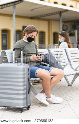 Young Man Wearing A Face Mask Looks At The Camera While Sitting At A Safe Distance Of A Young Woman