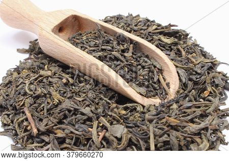 Closeup Of Dried Green Tea With Wooden Spoon On White Background. Healthy Lifestyles
