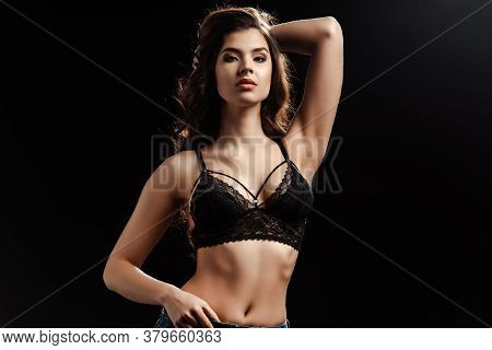 Sexy Woman In Lace Bra Looking At Camera Isolated On Black Background