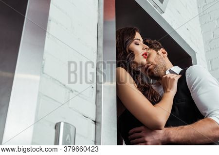 Focus Of Man In Waistcoat And Shirt Embracing Beautiful Girl Near Elevator