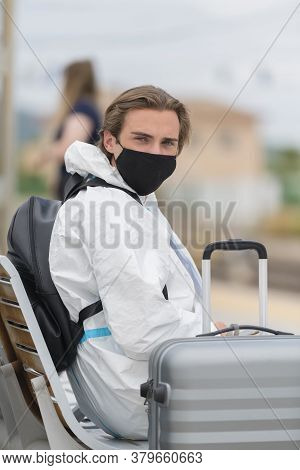 Young Man Wearing A Face Mask And A Protective Suit Waiting At A Train Station While Looking At The