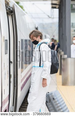 Young Man Wearing A Face Mask And A Protective Suit Carrying A Suitcase About To Enter A Train While