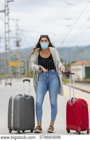 Young Woman With A Surgical Mask Surrounded By Two Suitcases Makes A Questioning Gesture At The Came