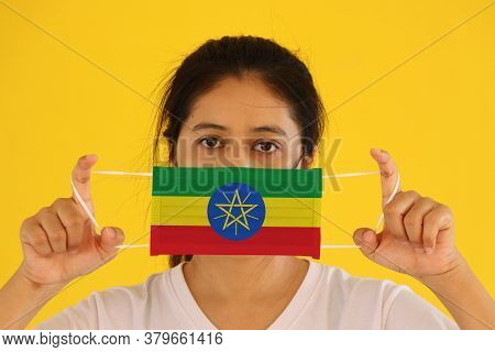 A Woman In White Shirt With Ethiopia Flag On Hygienic Mask In Her Hand And Lifted Up The Front Face