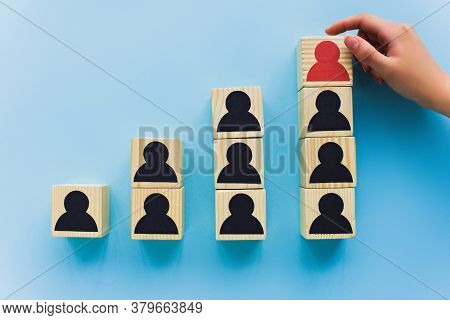 Partial View Of Hand Near Wooden Blocks With Black And Red Human Icons On Blue Background, Leadershi