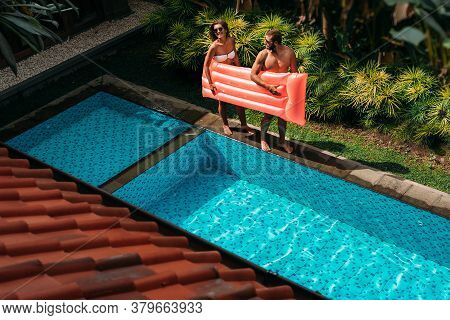 Couple Having Fun At The Swimming Pool. The Couple Is Relaxing By The Pool On Site. Couple Outside R