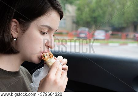 Young Beautiful Woman Eating Fast Food In The Car. Break. Dinner In The Car. Front Seat. Food Concep