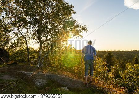 Young Man Walking On Rock With Tree With Sun Rays Shine. Ore Mountain, Czech Landscape