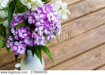 Bouquet Of Wildflowers In A Vase On A Wooden Background. Violet And White Flowers In A Vase.