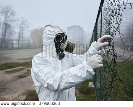 Close Up Of Male Scientist Tearing Torn Wire Fence. Man In Gas Mask And Protective Costume Standing